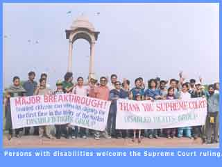 Picture of disabled persons with banners expressing approval of the Supreme Court judgement.