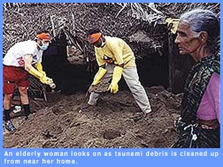 Picture of an elderly woman standing near the debris of her home