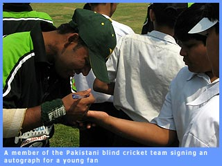Picture of a Pakistani blind cricketer signing an autograph for a young fan